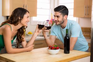 Two lovers stare into each others eyes on a date foreplay with conversation and a romantic mood with wine